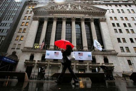People walk by the New York Stock Exchange (NYSE) during the morning commute in the financial district during a winter nor'easter in New York City, U.S., March 2, 2018. REUTERS/Andrew Kelly
