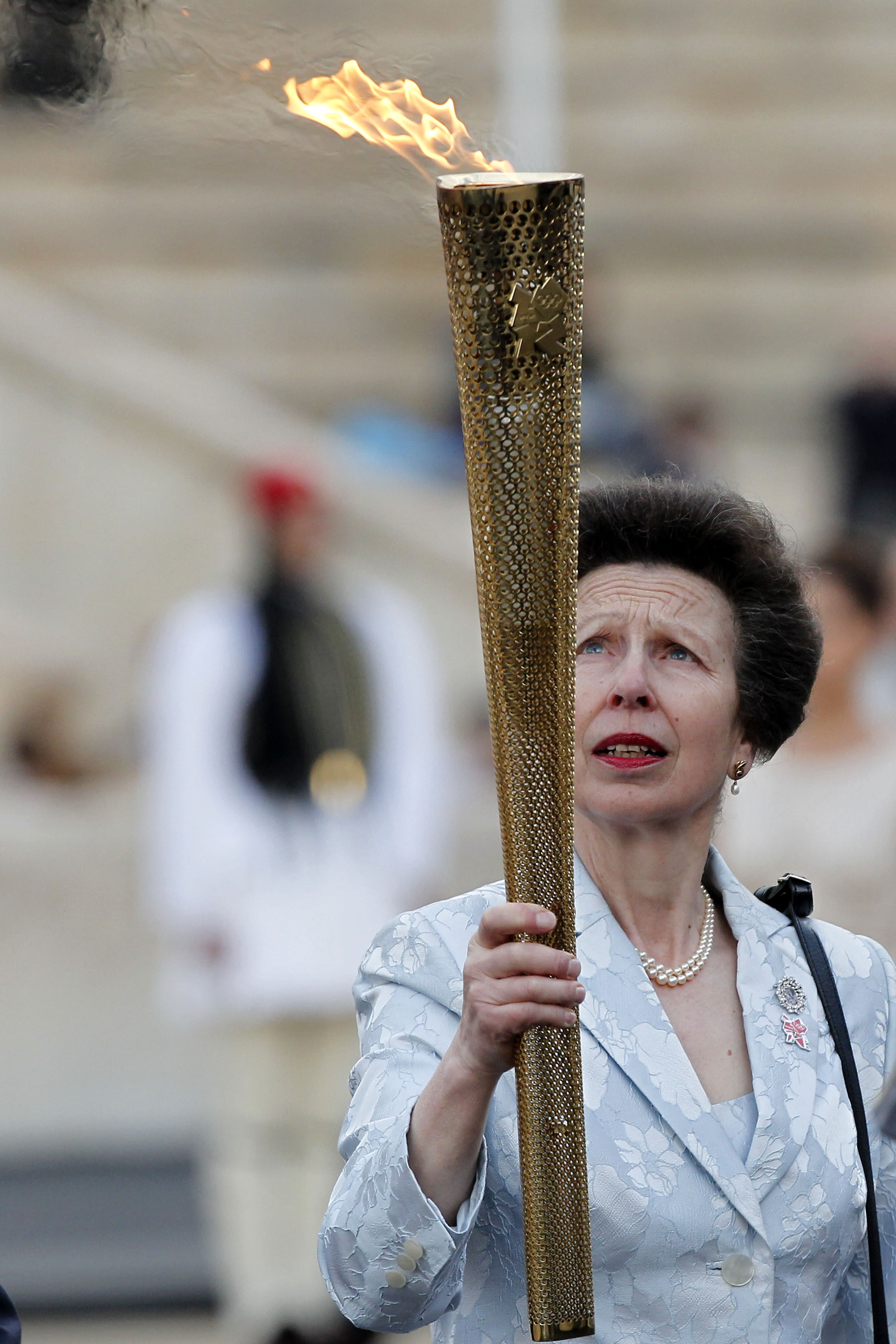 FILE - In this Thursday, May 17, 2012 file photo, Britain's Princess Anne holds the Olympic torch during the handover ceremony of the Olympic Flame in Panathenaic stadium in Athens. Queen Elizabeth II's only daughter, Princess Anne, will be celebrating her 70th birthday on Saturday, Aug. 15, 2020 in a no-nonsense manner that befits her reputation in Britain. Whatever is planned for Saturday, it's certainly going to be a scaled-back affair because of the coronavirus pandemic. (AP Photo/Petros Giannakouris, File)