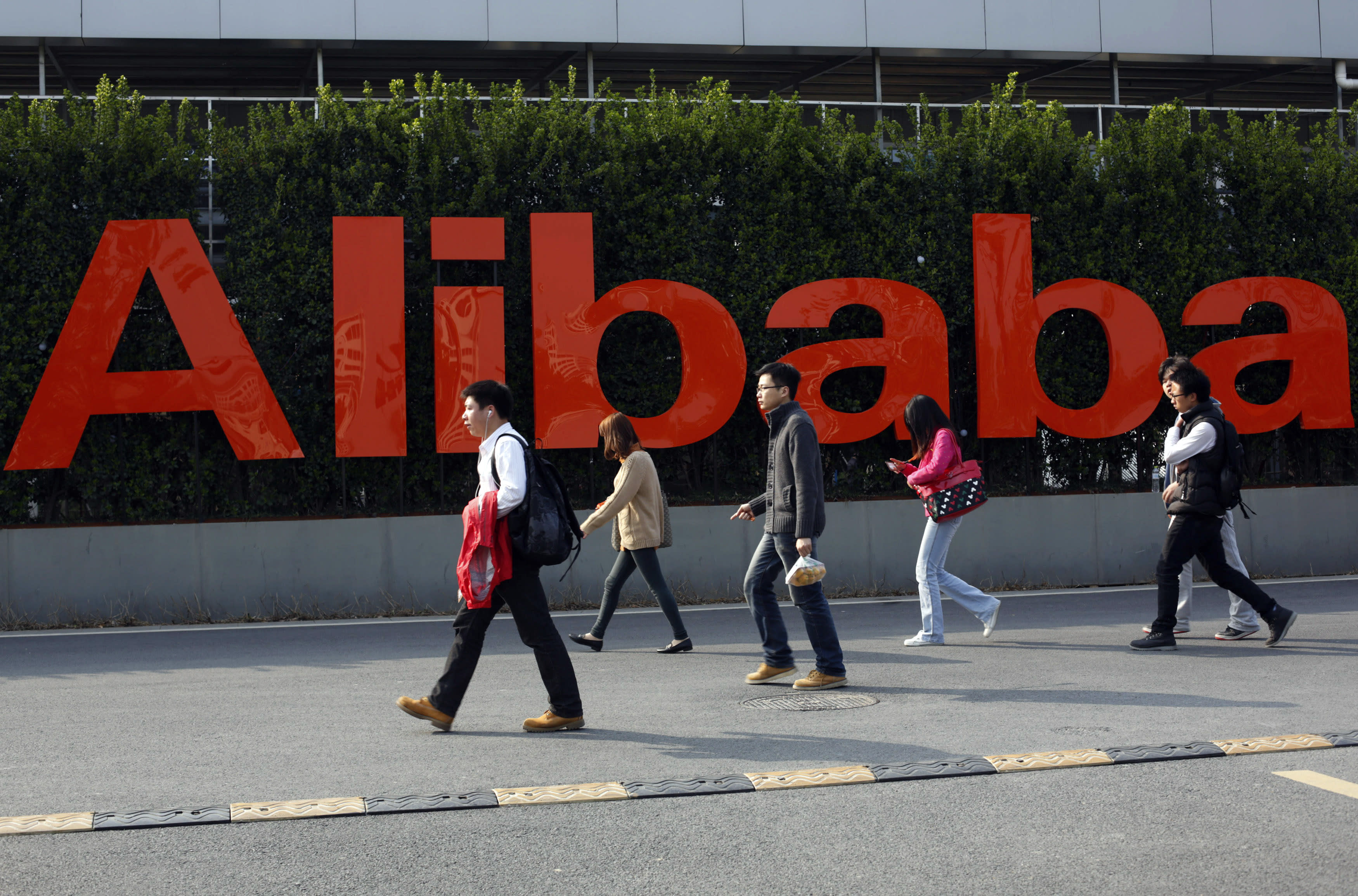 FILE - In this March 17, 2014 file photo, people walk past a company logo at the Alibaba Group headquarters in Hangzhou, in eastern China's Zhejiang province. Office Depot and Alibaba.com are creating a co-branded online store to expand the reach of both companies with small and medium size businesses. The two companies announced the agreement Monday, March 4, 2019, as part of a broader array of services they are providing to small business. Over time, the companies intend to help U.S. small businesses sell their products to buyers around the world through Alibaba.com. It marks Alibaba.com's first U.S. partnership with a major company. (Chinatopix via AP, File)