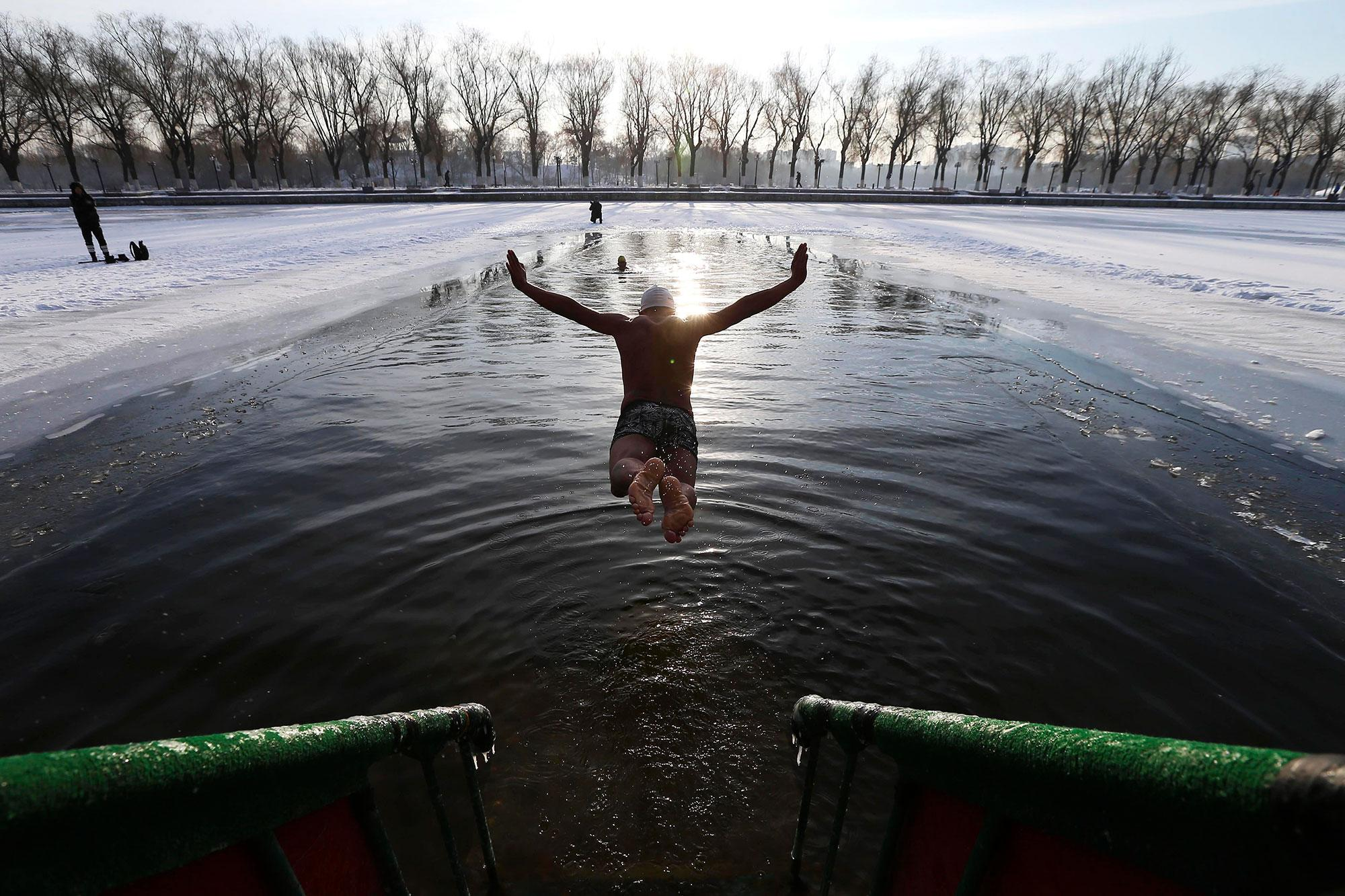 <p>A member of the Shenyang Beiling Winter Swimming team swims in a frozen lake in minus 20 degrees Celsius temperatures at Beiling park in Shenyang, Liaoning Province, China on Dec. 13, 2016. Ranging from from age 40 to 83, the 86 members of the Shenyang Beiling Winter Swimming team swim almost everyday even during minus freezing temperatures. Winter swimming is known to have many health benefits including improving blood circulation and heart conditions. (Photo: Tian Weitao/EPA) </p>