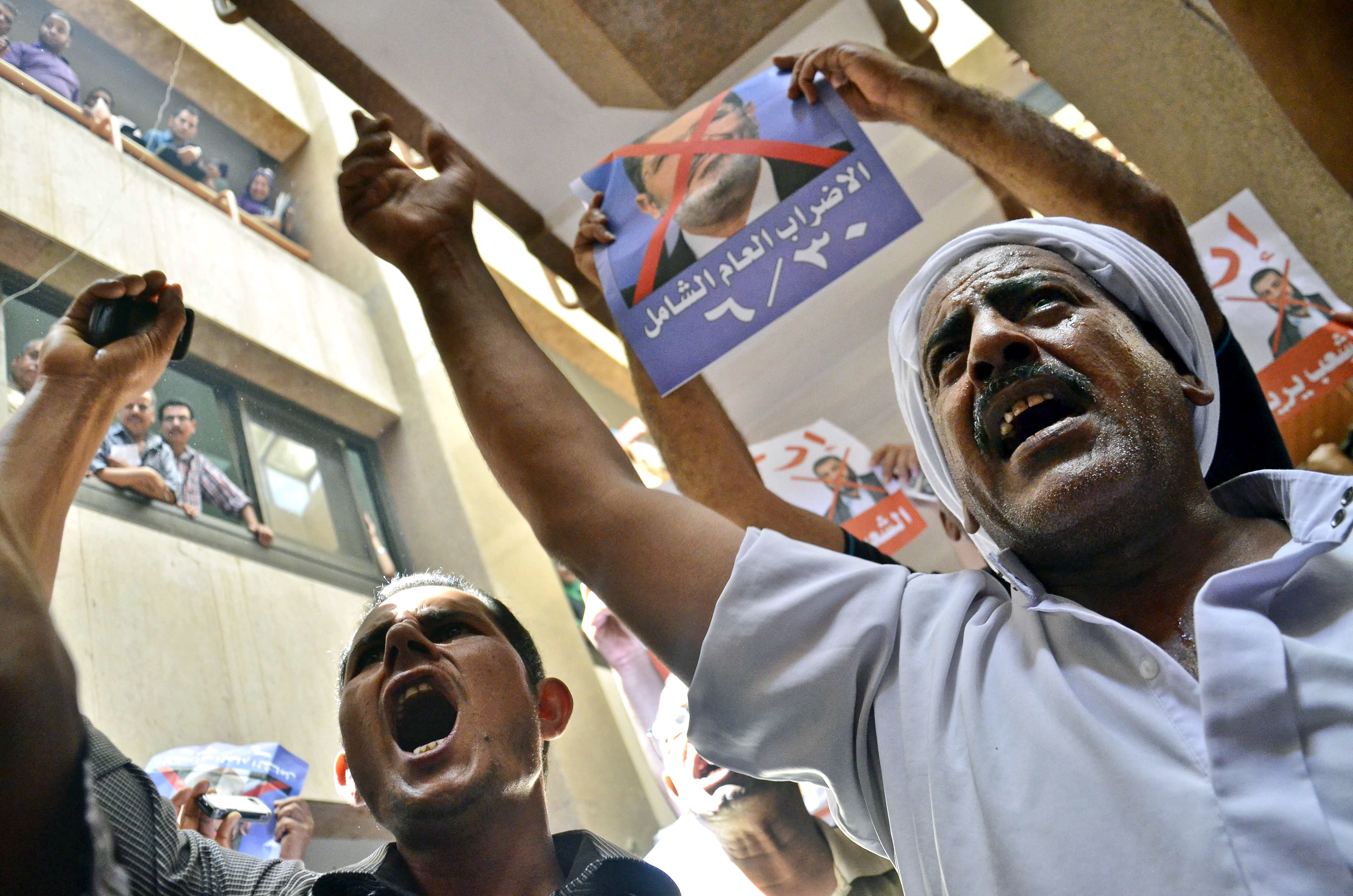 """Protesters chant slogans against Egyptian President Mohammed Morsi at a court in Ismailia, 139 Kilometers (86 miles) from Cairo, Egypt, Sunday, June 23, 2013. An Egyptian court on Sunday said Muslim Brotherhood members conspired with Hamas, Hezbollah and local militants to storm a prison in 2011 and free 34 Brotherhood leaders, including Morsi. The poster, top center, in Arabic reads, """"the biggest strike of the year, 6/30.""""(AP Photo/Mostafa Darwish)"""