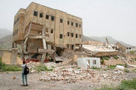 Journalist takes photos of a school destroyed by a Saudi-led air strike in the southwestern city of Taiz, Yemen
