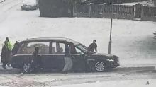 Heartwarming moment strangers push hearse up a hill after it got stuck in snow