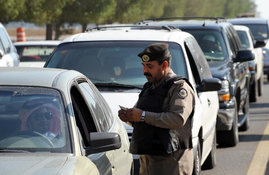 A Saudi policeman checks the ID card of a driver at a checkpoint in the mostly Shiite Qatif region