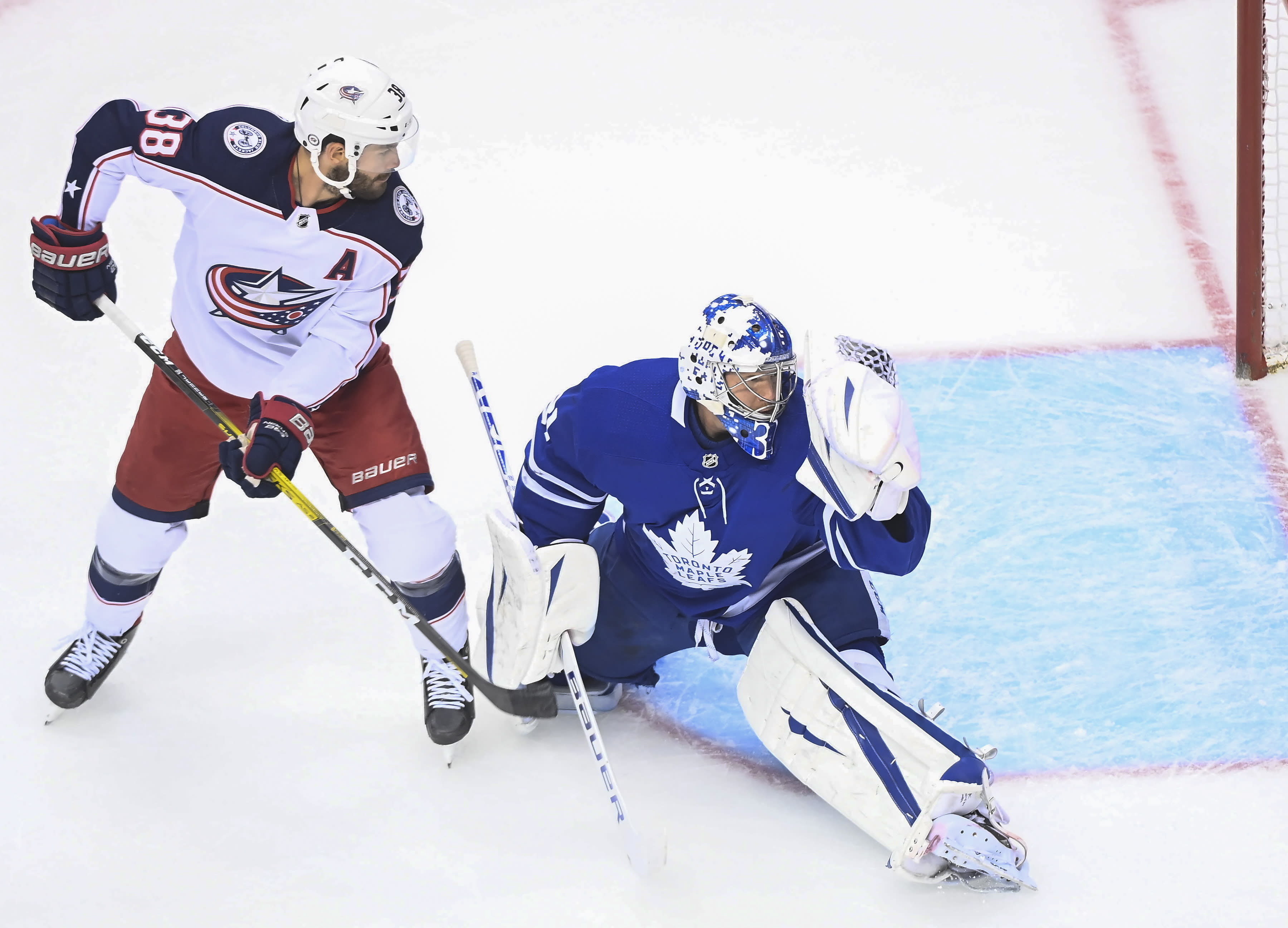 Toronto Maple Leafs goaltender Frederik Andersen (31) makes a glove save as Columbus Blue Jackets center Boone Jenner (38) looks on during the first period of an NHL Eastern Conference Stanley Cup playoff game in Toronto on Sunday, Aug. 9, 2020. (Nathan Denette/The Canadian Press via AP)