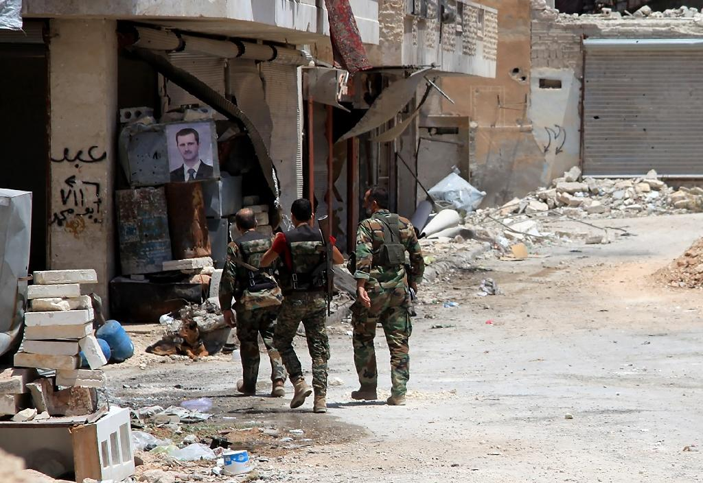 Syrian army soldiers patrol in government-controlled Aleppo's al-Khalidiya area where the army progressed towards the industrial zone of al-Layramoun and Bani Zeid on June 28, 2016