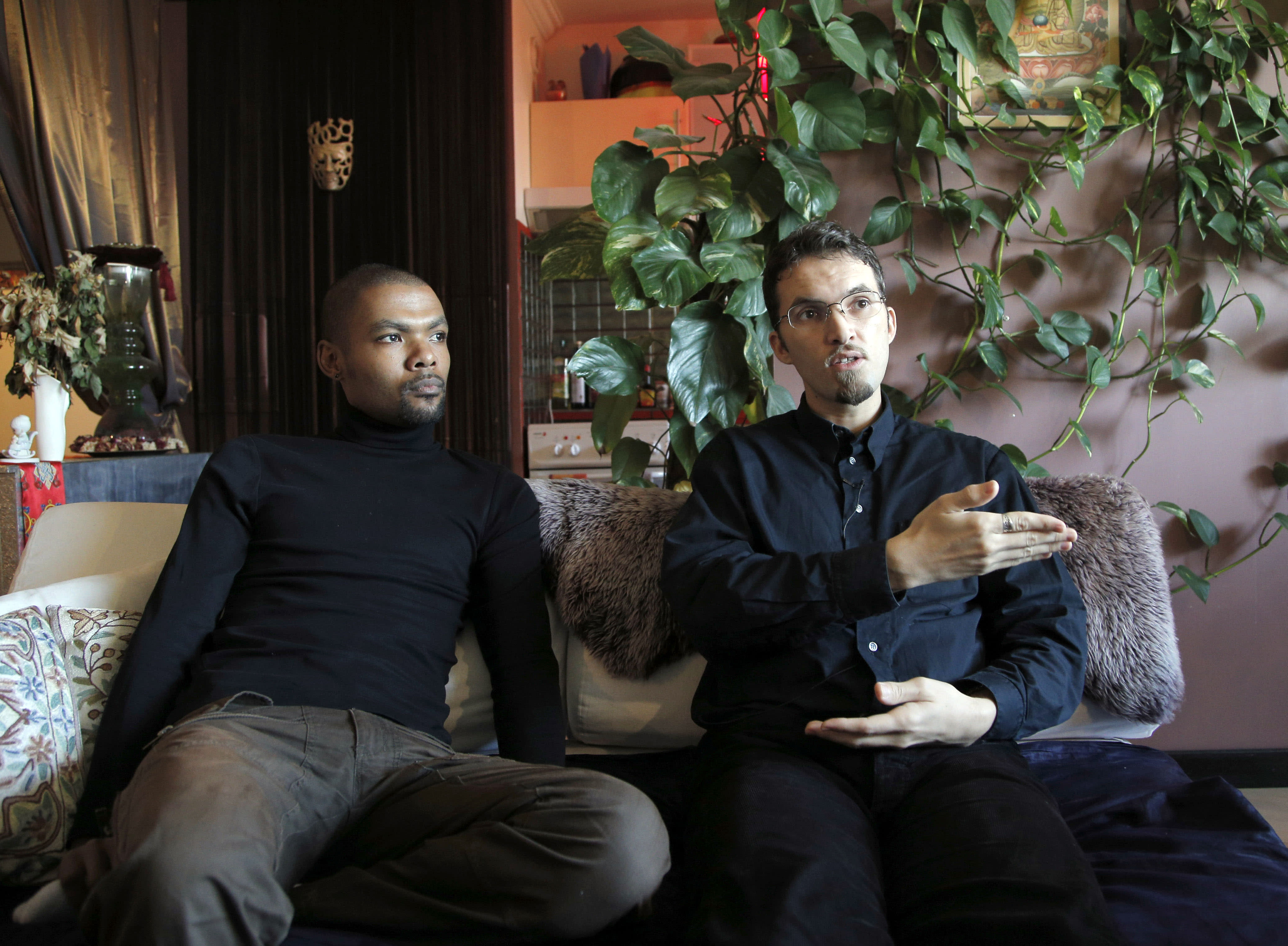 """In this photo taken on Monday, Oct. 22, 2012, Ludovic-Mohamed Zahed, right, who married his live-in partner Qiyaammudeen Jantjies, left, in South Africa, where gay marriage is recognized, during an interview with the Associated Press in Sevran, outside Paris. A plan to legalize same-sex marriage and allow gay couples to adopt was a liberal cornerstone of French President Francois Hollande's election manifesto earlier this year. It looked like a shoo-in, supported by a majority of the French, and an easy way to break with his conservative predecessor. But that was then, Now, as the Socialist government prepares to unveil its draft """"marriage for everyone"""" law Wednesday, polls show wavering support for the idea and for the president amid increasingly vocal opposition in this traditionally Catholic country. Ludovic-Mohamed Zahed, who married his live-in partner Qiyaammudeen Jantjies in South Africa, where gay marriage is recognized, is already seeking instruction from his local town council to get his marriage recognized in France as soon as he can. (AP Photo/Christophe Ena)"""