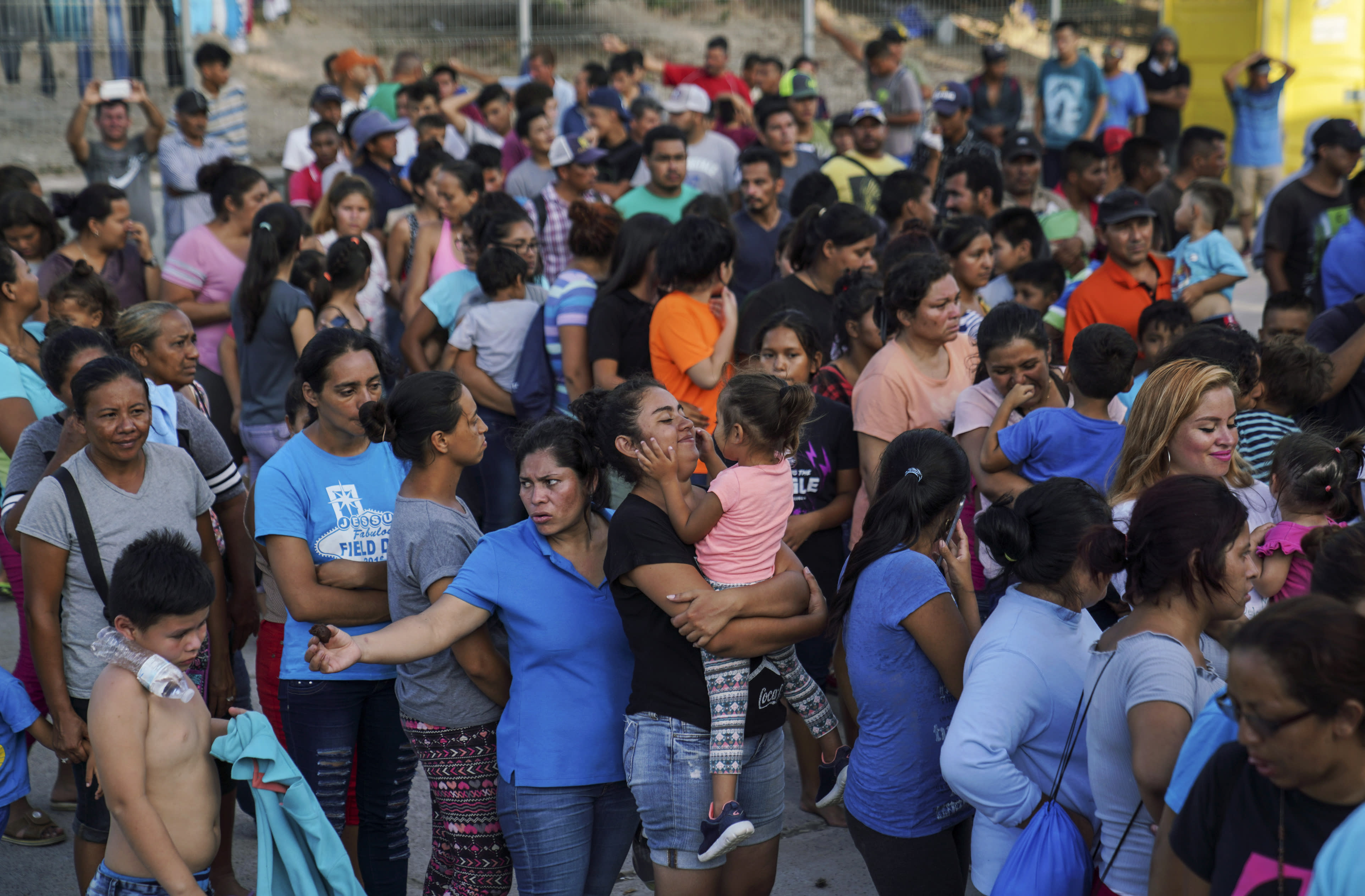 """In this Aug. 30, 2019, photo, migrants, many who were returned to Mexico under the Trump administration's """"Remain in Mexico,"""" program wait in line to get a meal in an encampment near the Gateway International Bridge in Matamoros. Many shelters at the Mexico border are at or above capacity already, and some families have been sleeping in tents or on blankets in the blistering summer heat. (AP Photo/Veronica G. Cardenas)"""