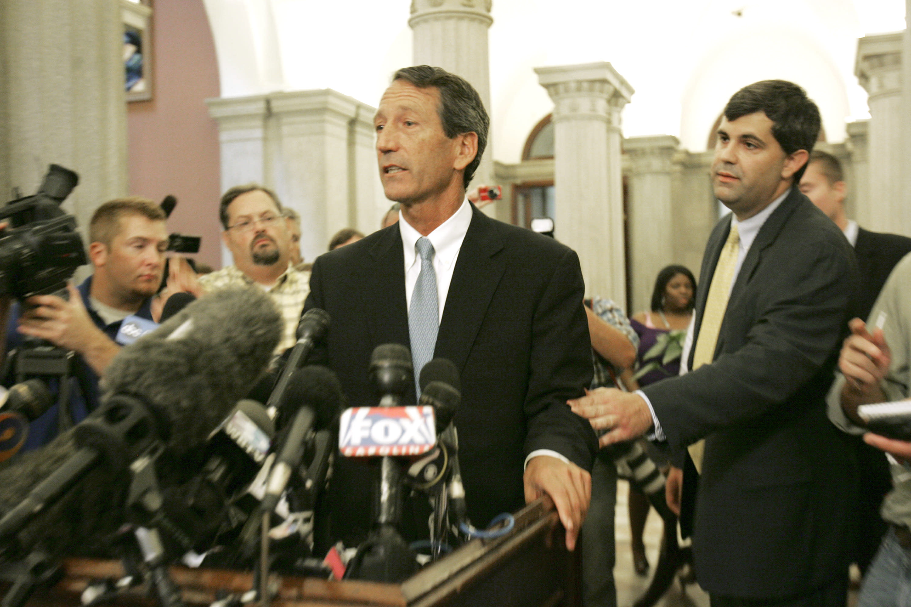 Joel Sawyer, right, grabs then South Carolina Gov. Mark Sanford's arm as he continues to answer questions after he admitted to having an affair during a news conference Wednesday, June 24, 2009, in Columbia, S.C. (AP Photo/Mary Ann Chastain)