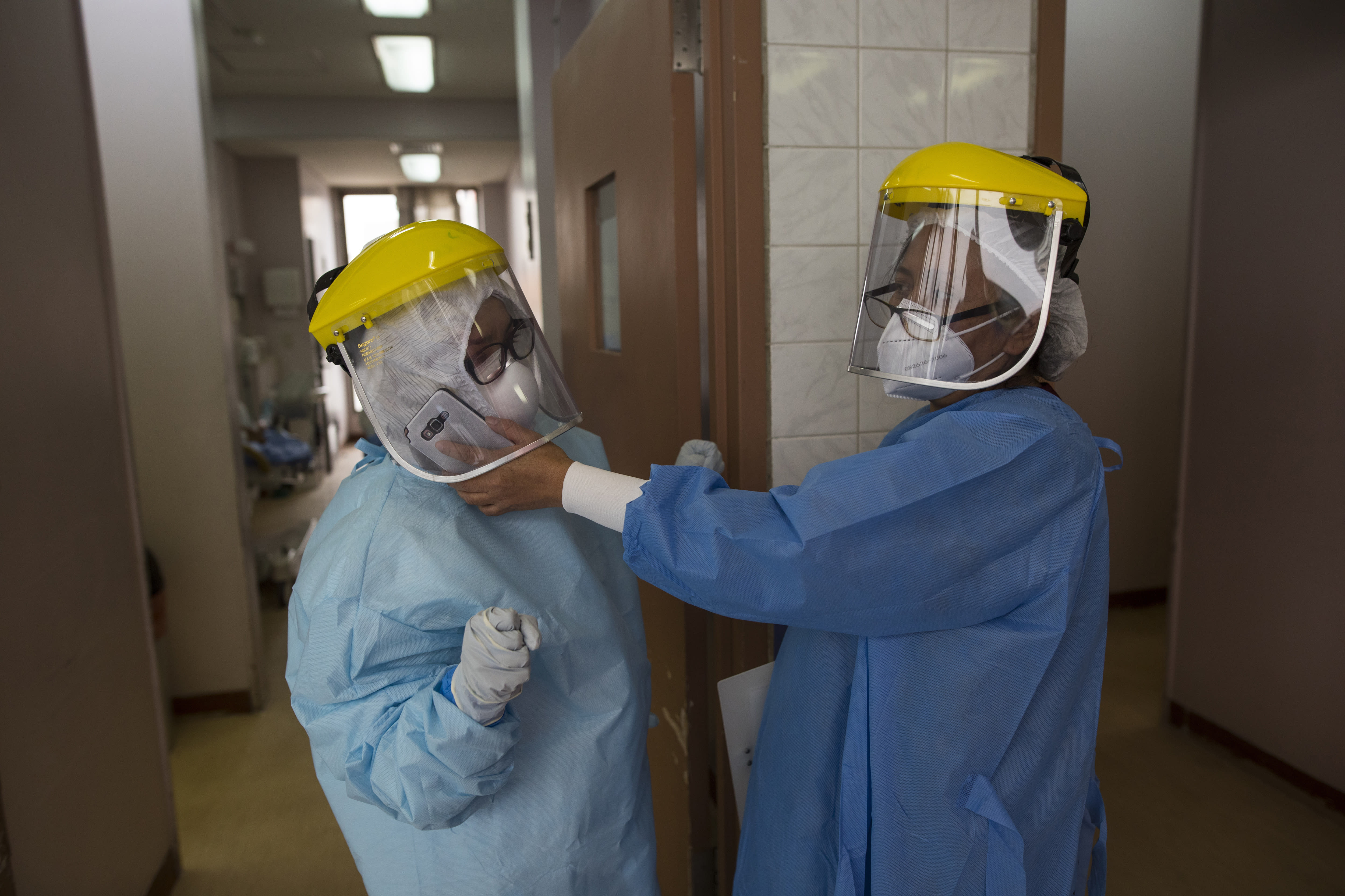 A healthcare worker helps a fellow obstetrician receive a phone call making her rounds in a special ward for mothers with COVID-19, at the National Perinatal and Maternal Institute, in Lima, Peru, Thursday, July 9, 2020. Despite wearing personal protective equipment and taking other measures to avoid infection, 400 of the 2000 Institute's workers have also been infected, said its director, Enrique Guevara. (AP Photo/Rodrigo Abd)