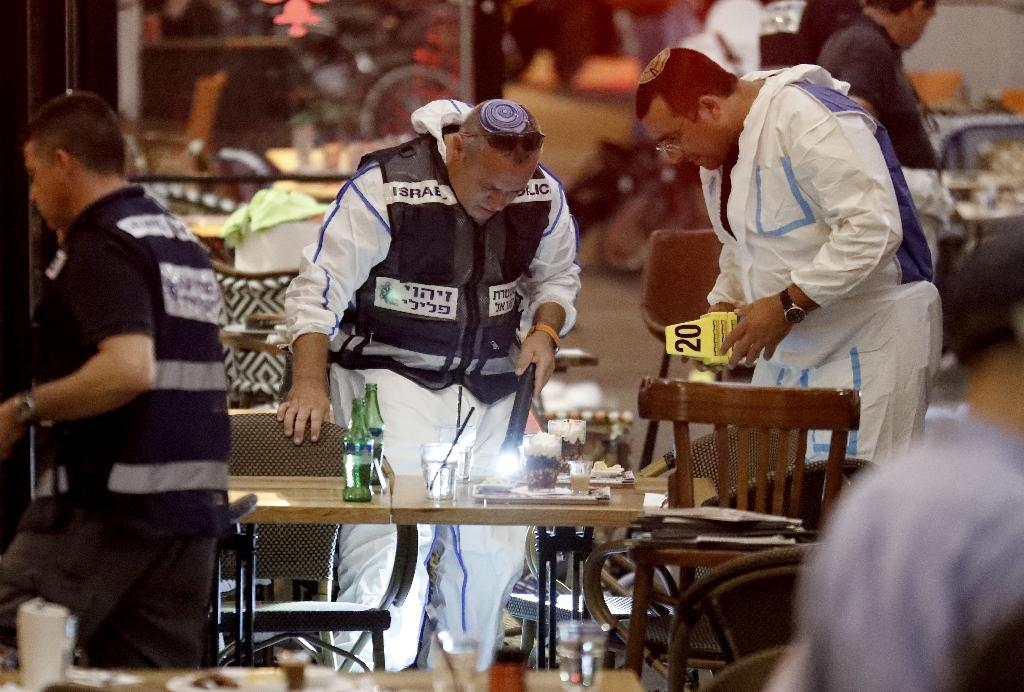 Israeli forensic police inspect a restaurant following a shooting attack which left four people dead in Tel Aviv on June 8, 2016 At least three people were killed and several wounded in the shooting spree, emergency services said. Police said that it appeared to be a militant attack, but they could not immediately give any details of the attacker or victims. (AFP Photo/Jack Guez)