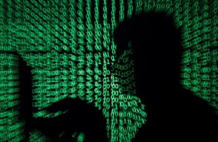 FILE PHOTO: Man holds laptop computer as cyber code is projected on him in this illustration picture