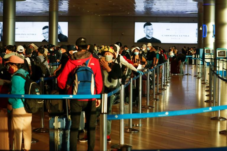 Passengers queue at Israel's Ben Gurion airport to board a plane out of the virus-hit country ahead of the government's decision to slap restrictions on all outgoing flights