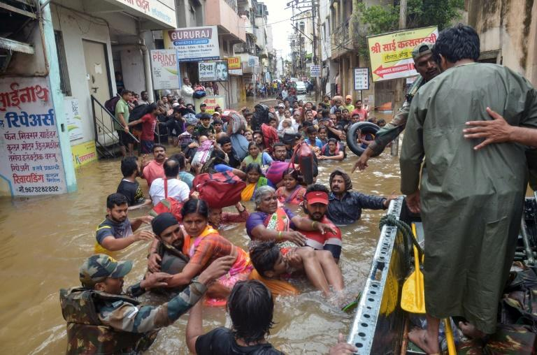 Army personnel rescue people stranded in flood waters in Sangli in Maharashtra state, which has been badly hit by the monsoon rains (AFP Photo/Uday DEOLEKAR)