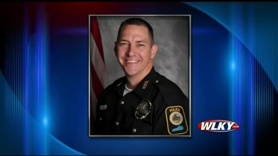 Community mourns as police search for officer's killer