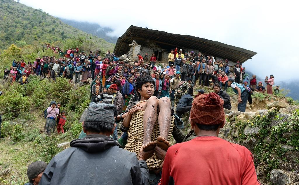 Villagers carry an injured youth in a basket down the hill-side to an Indian Army helicopter at Uiya village, in northern-central Gorkha district on April 29, 2015 (AFP Photo/Sajjad Hussain)