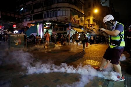 People run away from tear gas fired by police to disperse anti-extradition bill protesters demonstration at Sham Shui Po