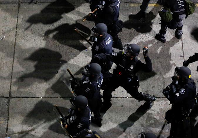 A Seattle Police officer throws a canister towards protesters during a protest against racial inequality in the aftermath of the death in Minneapolis police custody of George Floyd, near the Seattle Police department's East Precinct in Seattle, Washington, U.S. June 8, 2020. REUTERS/Lindsey Wasson