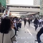 Bystanders in Hong Kong's Central District Applaud as Protesters Run By