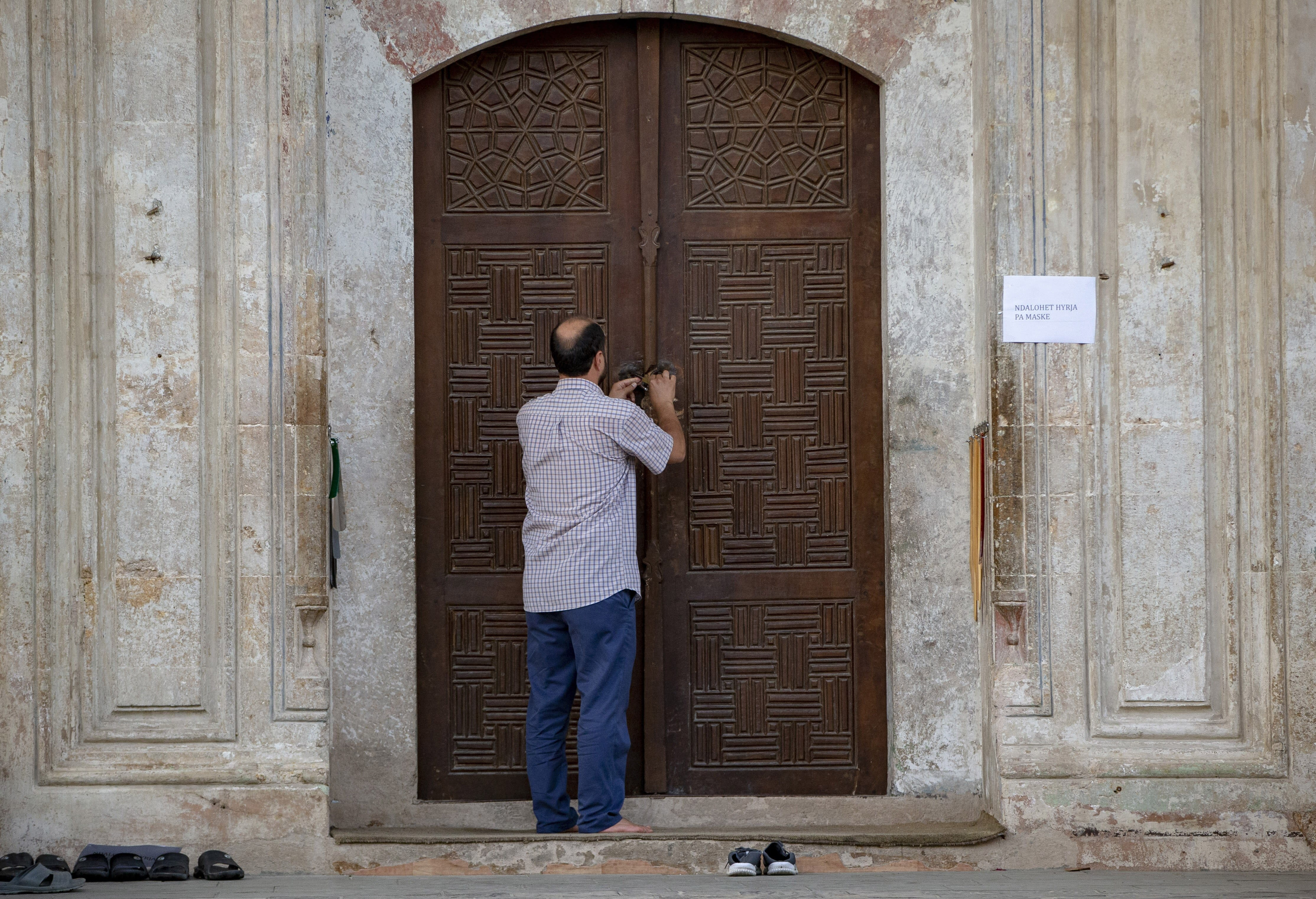 An employee of the Kosovo Islamic Community closes the door of the Sultan Mehmet Fatih mosque in Pristina, Kosovo, Friday, July 31, 2020. Government measures banned all public gatherings including religious due to fear of recent uprise in COVID-19 cases. (AP Photo/Visar Kryeziu)