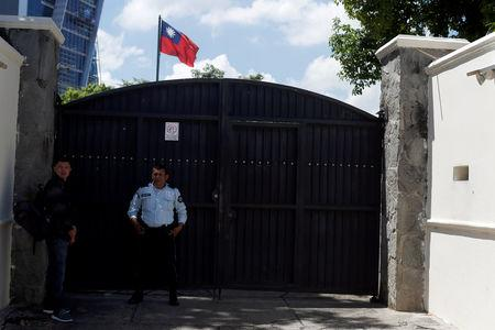 FILE PHOTO - A man waits to visit the Taiwan embassy a day after the Salvadoran government announced that it has broken off diplomatic relations with Taiwan, in San Salvador