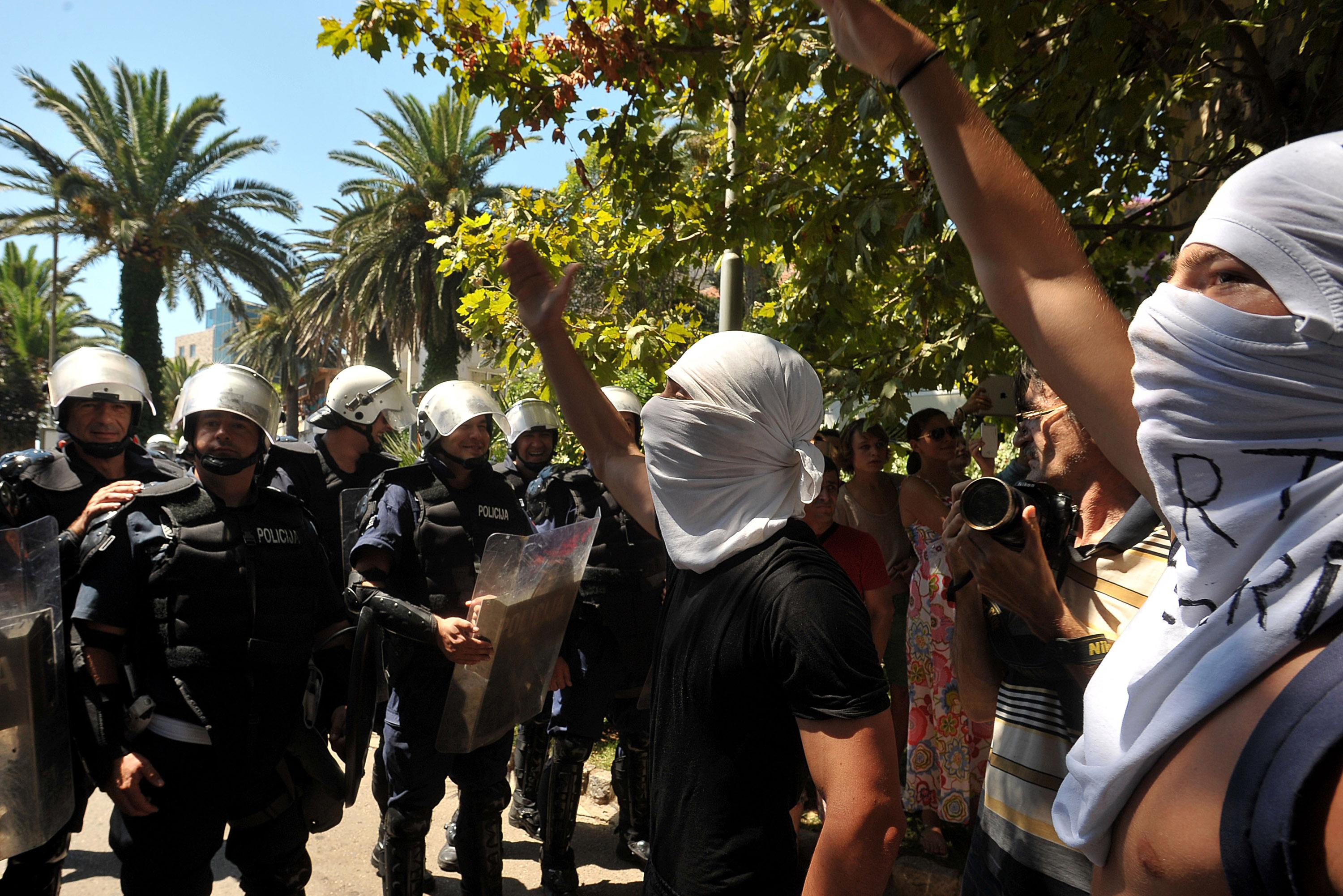 "Protesters shout slogans during the first ever pride event in the Montenegrin seaside resort of Budva, Wednesday, July 24, 2013. Dozens of extremists shouting ""Kill the gays"" have attacked gay activists as they were gathering for the first ever pride event in staunchly conservative Montenegro. The assailants threw rocks, bottles and various other objects at some 20 gay activists and supporters and at special police securing the event in the coastal town of Budva on Wednesday. Police intervened to push the attackers away and the event continued as planned. (AP Photo/Risto Bozovic)"