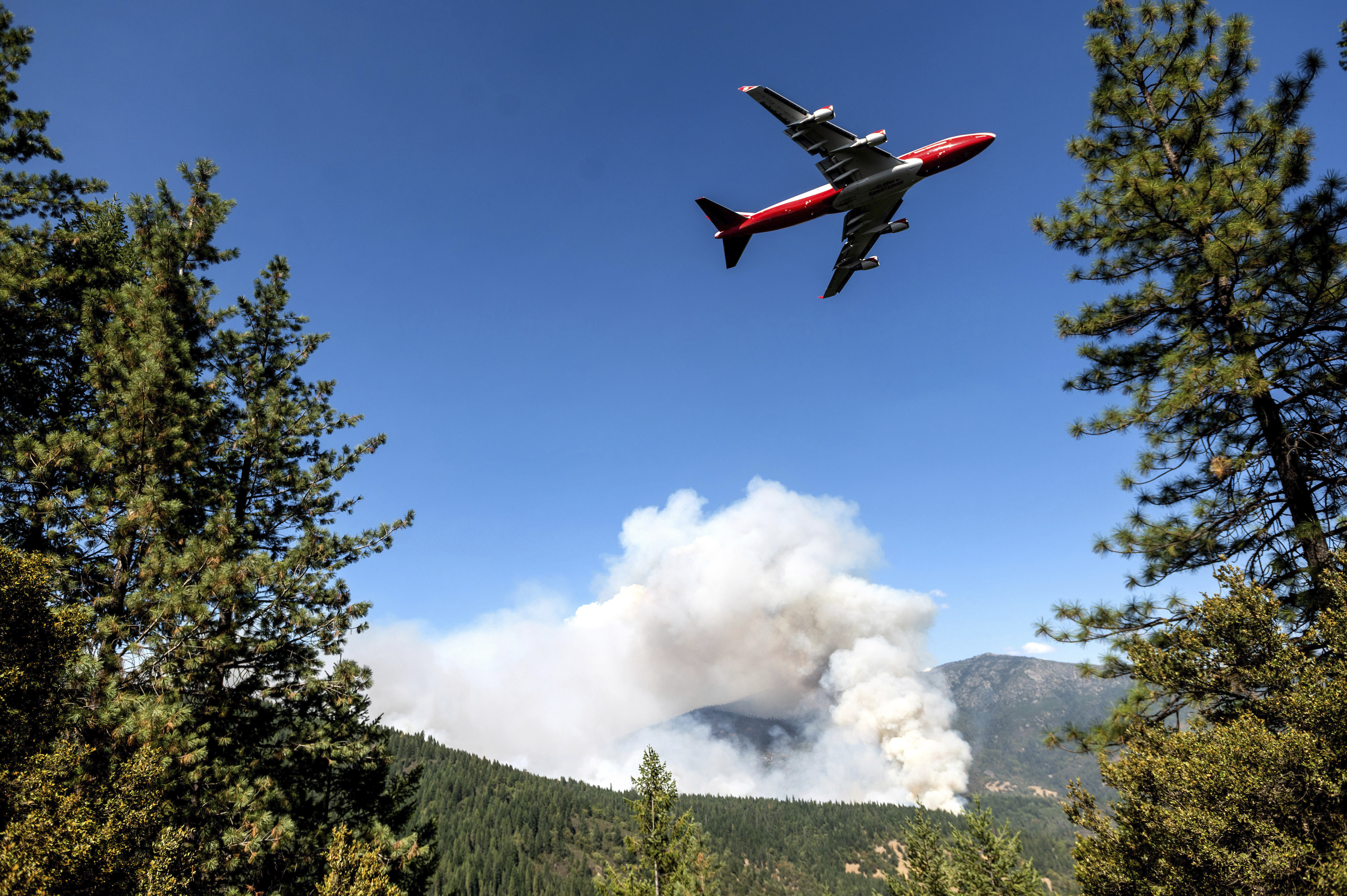 FILE - In this Sept. 17, 2020, file photo, an air tanker prepares to drop retardant while battling the August Complex Fire in the Mendocino National Forest, Calif. Rain showers fell Thursday, Sept. 24, 2020, on the northwestern edges of fire-ravaged California but forecasters warned residents to not be fooled: a new round of hot, dry and windy weather is expected by the weekend. (AP Photo/Noah Berger, File)