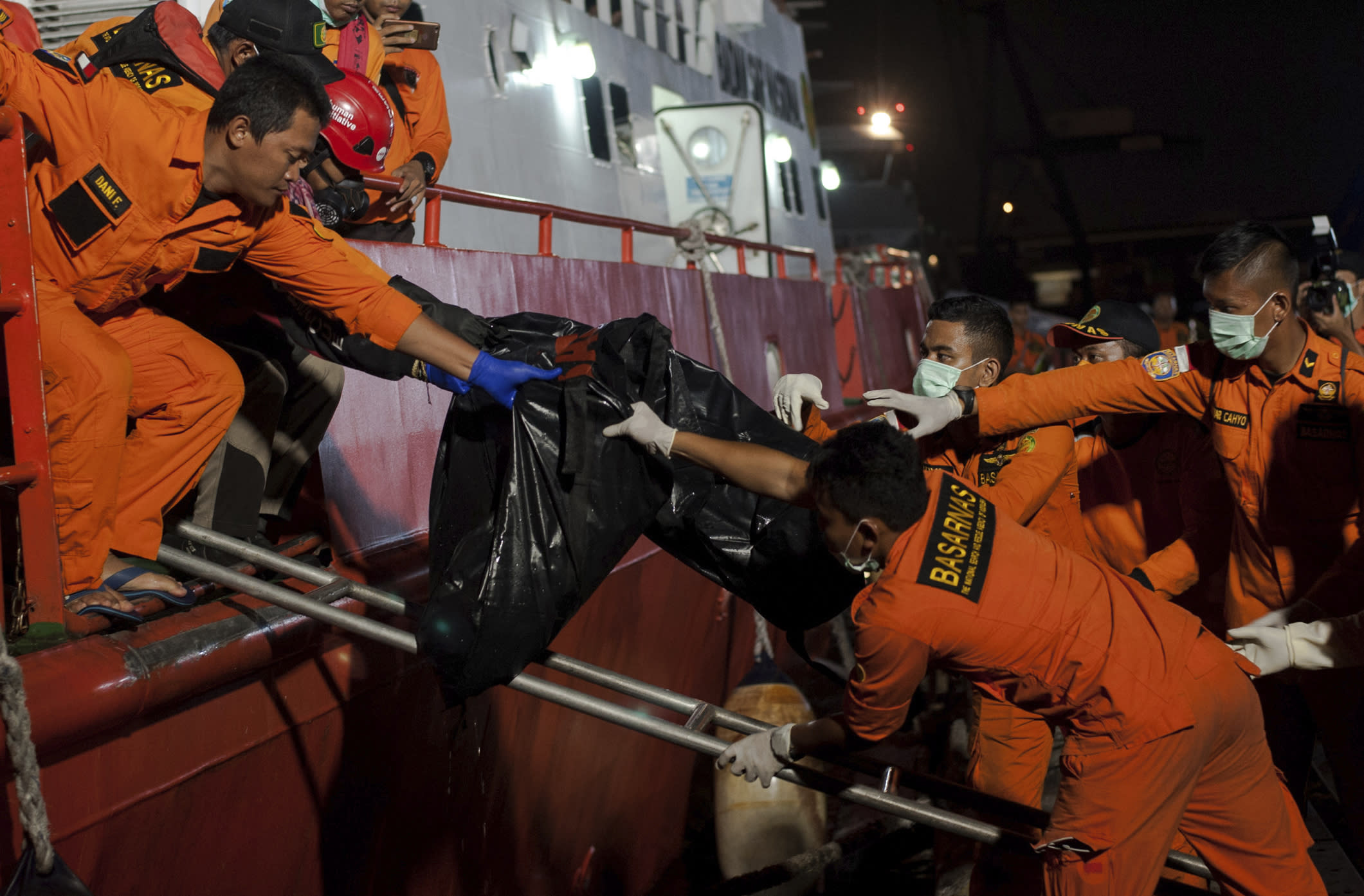 Rescuers hand body bags containing the remains of the victims of the crashed Lion Air jet to colleagues upon arrival at Tanjung Priok Port in Jakarta, Indonesia, Saturday, Nov. 3, 2018. The brand new Boeing 737 MAX 8 jet plunged into the Java Sea just minutes after takeoff from Jakarta early on Oct. 29, killing all of its passengers on board. (AP Photo/Fauzy Chaniago)