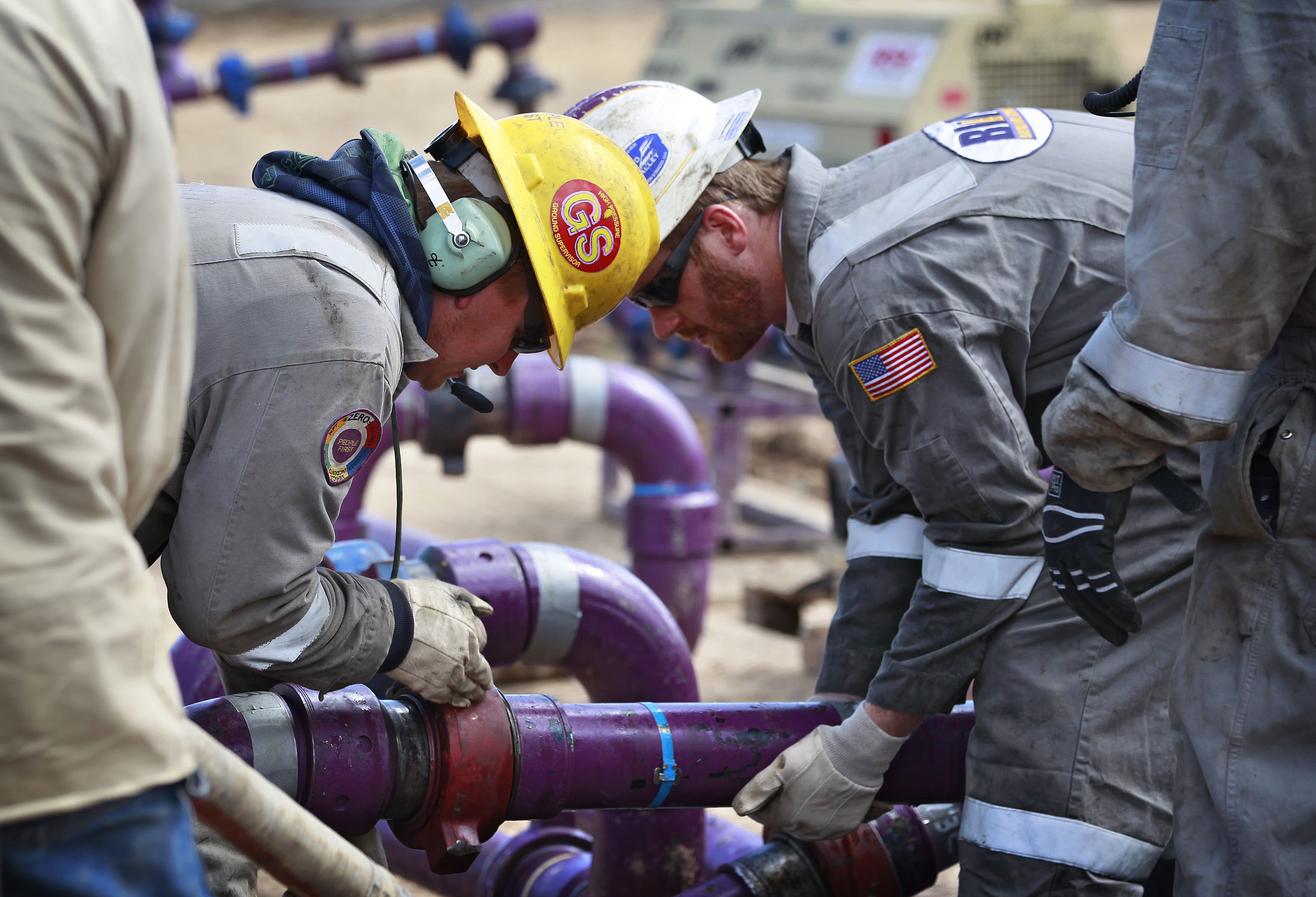 In this March 29, 2013, photo, workers adjust piping during a short pause in water pumping during a natural gas hydraulic fracturing operation at an Encana Oil & Gas (USA) Inc. drilling site outside Rifle, in western Colorado. The first experimental use of hydraulic fracturing was in 1947, and more than 1 million U.S. oil and gas wells have been fracked since, according to the American Petroleum Institute. The National Petroleum Council estimates up to 80 percent of natural gas wells drilled in the next decade will require hydraulic fracturing. (AP Photo/Brennan Linsley)