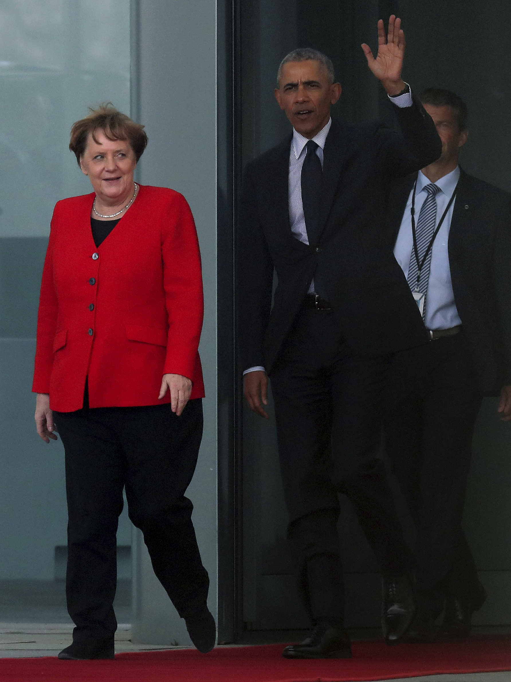 Former US President Barack Obama, right, waves as he and German Chancellor Angela Merkel, left, leave the Chancellery after a meeting in Berlin, Germany, Friday, April 5, 2019. (AP Photo/Michael Sohn)