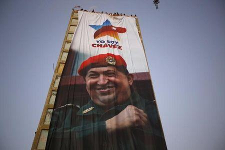 Supporters of Venezuela's late president Hugo Chavez display his image on a banner on a building, during the first anniversary of his death in Caracas
