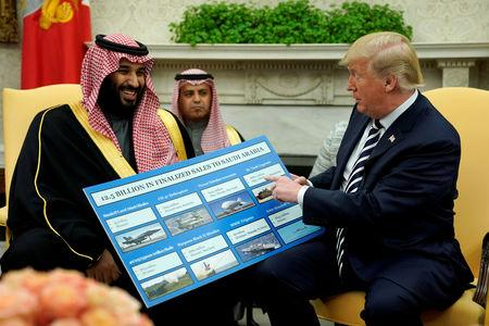 FILE PHOTO: U.S. President Donald Trump holds a chart of military hardware sales as he welcomes Saudi Arabia's Crown Prince Mohammed bin Salman in the Oval Office at the White House in Washington, U.S., March 20, 2018. REUTERS/Jonathan Ernst/File Photo