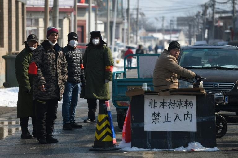 Residents stand at the entrance to their village, blocked off to prevent the spread of the coronavirus, at Jiuduhe, north of Beijing