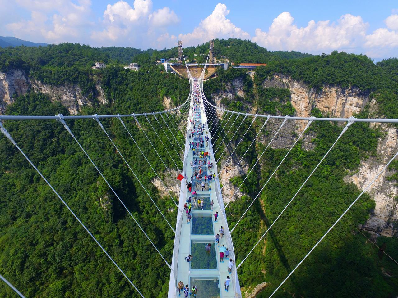 <p>Aerial view photo shows tourists visiting on the glass-bottom bridge at Zhangjiajie Grand Canyon on August 20, 2016 in Zhangjiajie, Hunan Province of China. (Photo: VCG/VCG via Getty Images)</p>