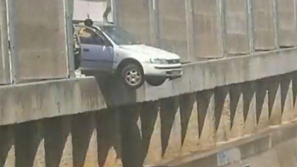 Car dangles over train tracks after crashing through wall in Sydney
