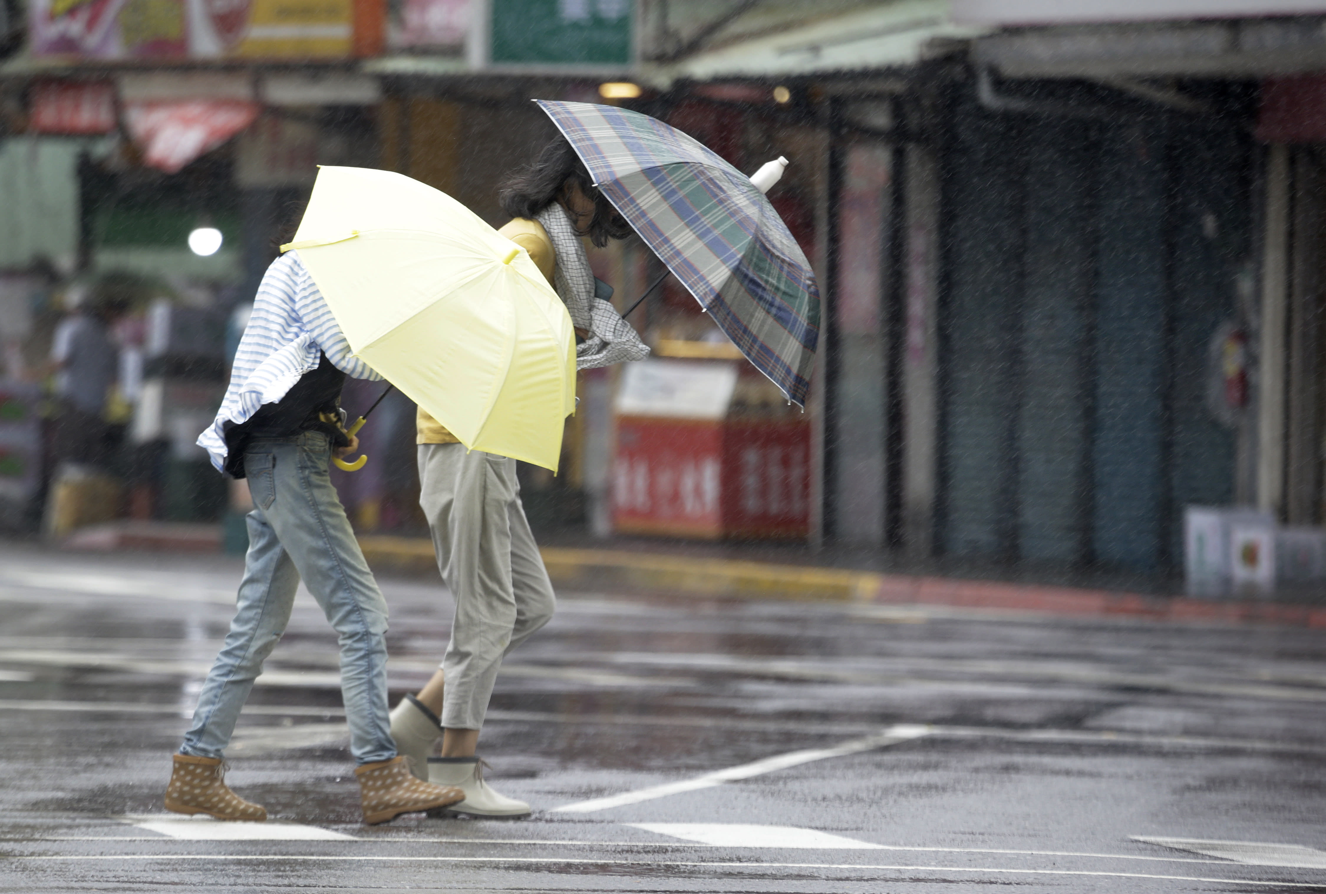 Two Taiwanese women make their way against powerful gusts of wind generated by typhoon Lekima in Taipei, Taiwan, Friday, Aug. 9, 2019. (AP Photo/Chiang Ying-ying)