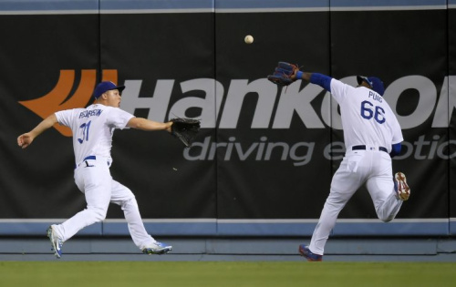 Los Angeles Dodgers right fielder Yasiel Puig, right, makes a catch on a ball hit by St. Louis Cardinals' Yadier Molina before colliding with center fielder Joc Pederson during the 10th inning of a baseball game, Tuesday, May 23, 2017, in Los Angeles. (AP Photo/Mark J. Terrill)
