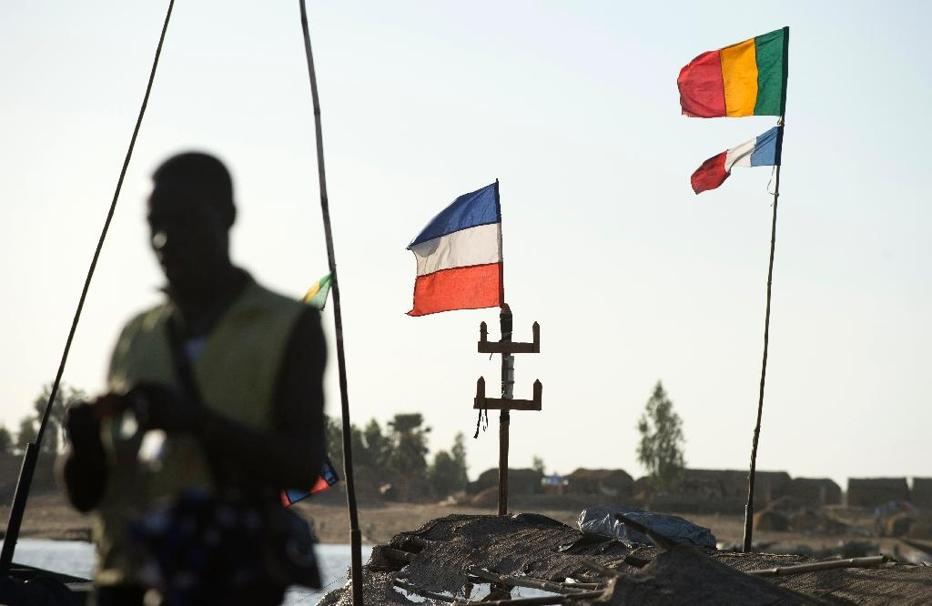 French and Malian flags fly over so-called Pinasse boat on the river Bani, a branch of the river Niger, at the commercial port of the central Malian city of Mopti on March 15, 2013