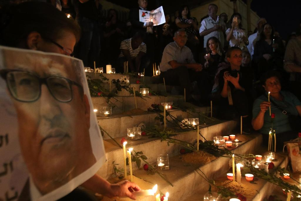 Jordanians light candles for prominent writer Nahed Hattar (portrait L), who was shot dead outside an Amman court (AFP Photo/Khalil Mazraawi)