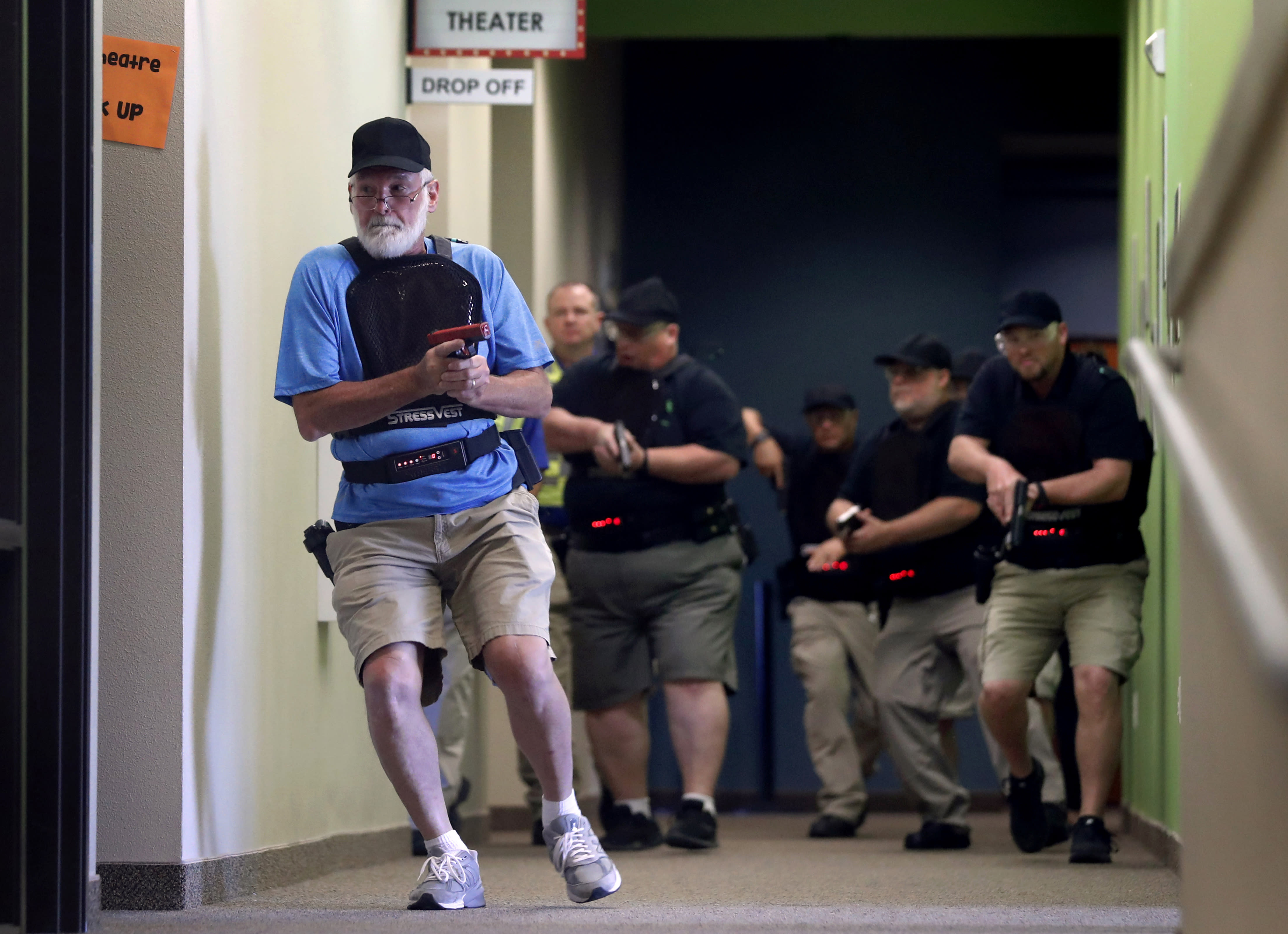 In this July 21, 2019 photo, Stephen Hatherley, left, leads fellow trainees down a hallway as they participate in a simulated gun fight scenario at Fellowship of the Parks campus in Haslet, Texas. While recent mass shootings occurred at a retail store in El Paso, Texas, and a downtown entertainment district in Dayton, Ohio, they were still felt in houses of worship, which haven't been immune to such attacks. And some churches have started protecting themselves with guns. (AP Photo/Tony Gutierrez)