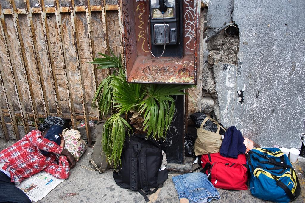 A migrant seeking asylum in the United States, sleeps on the sidewalk on the Mexican side of the San Isidro Port of Entry, in Tijuana, northwestern Mexico (AFP Photo/Guillermo Arias)