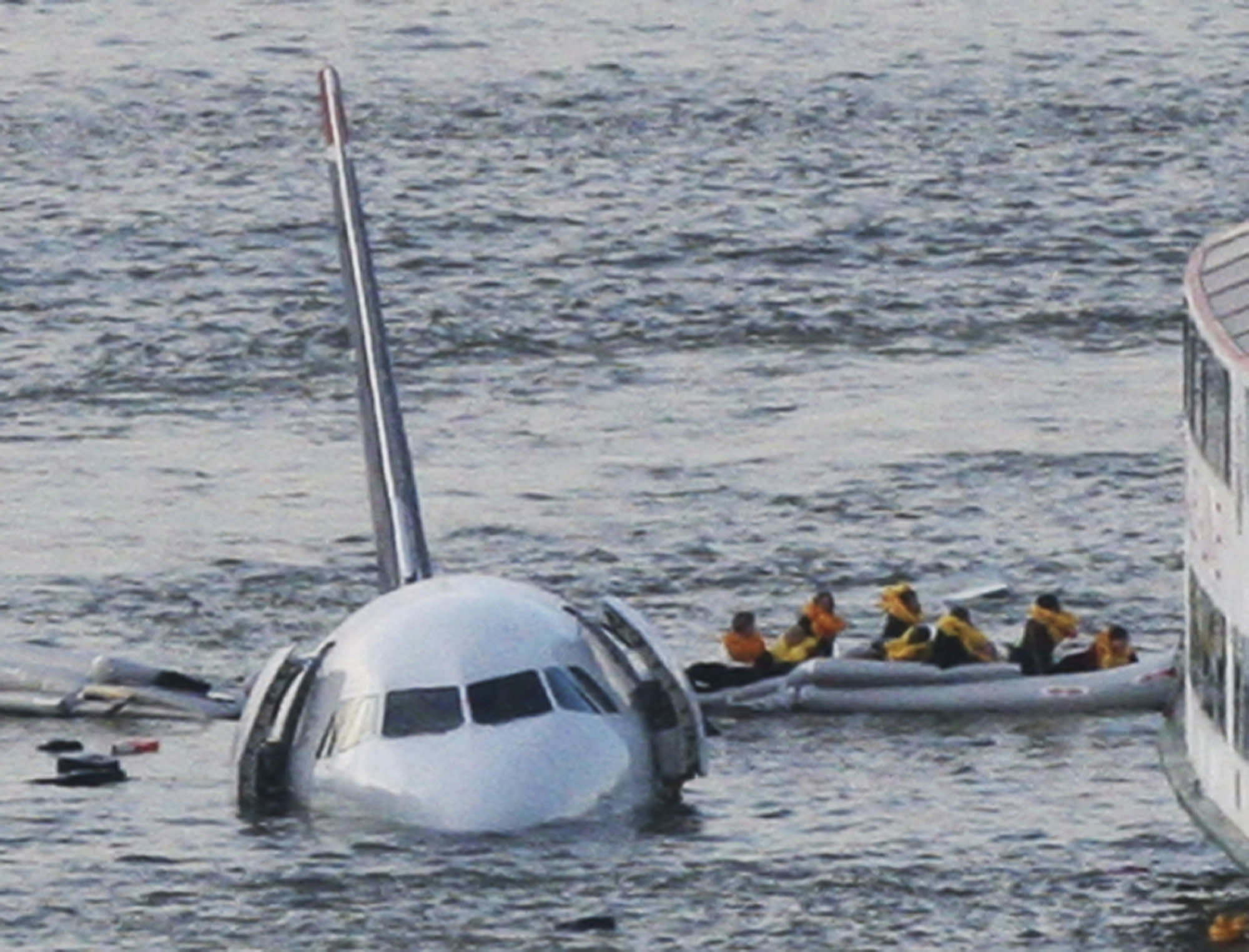 FILE - In this Jan. 15, 2009 file photo, passengers in an inflatable raft move away from an Airbus 320 US Airways aircraft that has gone down in the Hudson River in New York. Passengers in plane crashes like the Aeromexico accident on Tuesday, July 31, 2018, in which no one died, have better chances of survival due to better aircraft construction and safety standards, experts say. (AP Photo/Bebeto Matthews, File)