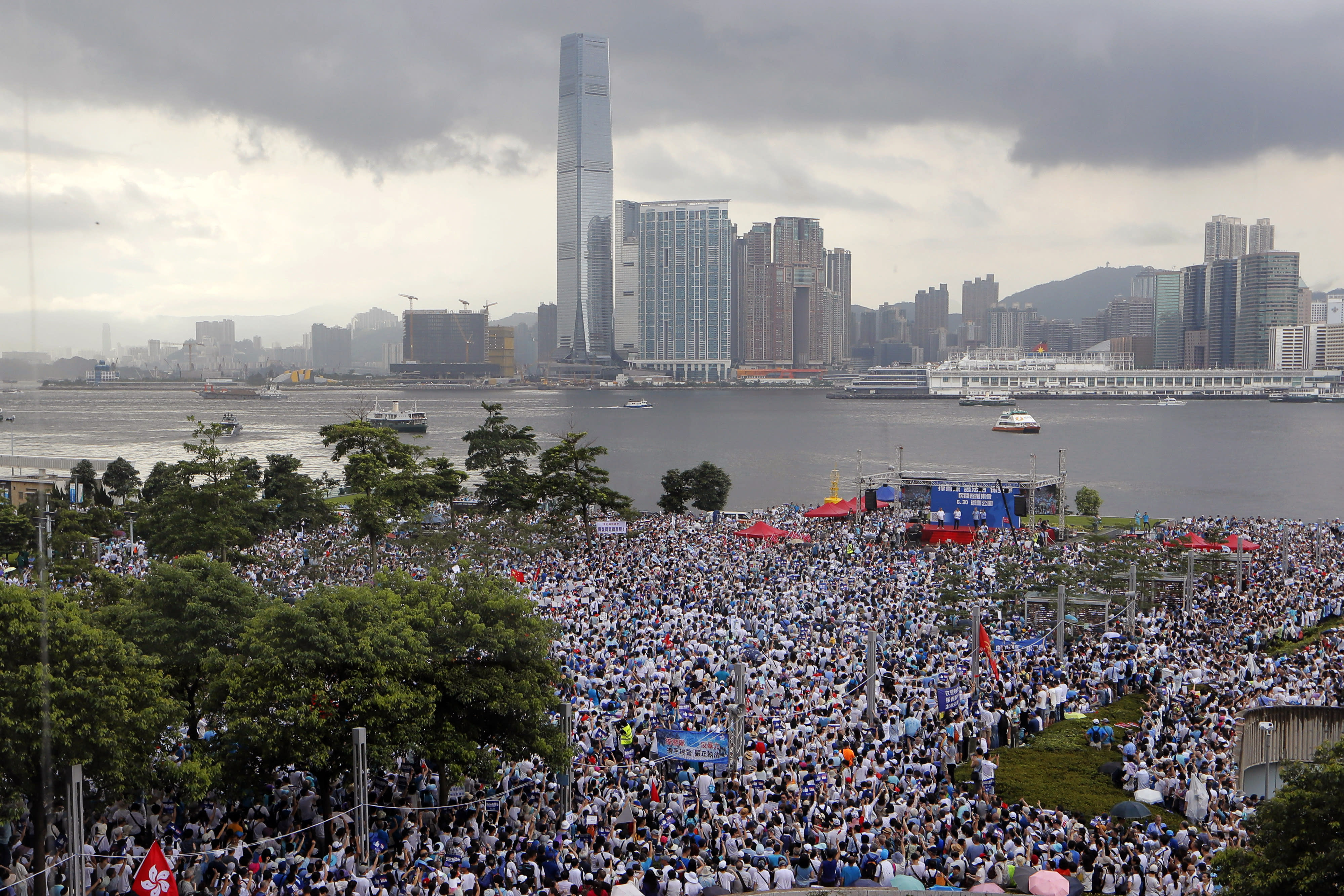 """Pro-China's supporters hold Chinese flags and placards read """"We support police"""" during a rally outside Legislative Council Complex in Hong Kong, Sunday, June 30, 2019. Supporters rallied in support of the police at Tamar Park (AP Photo/Kin Cheung)"""