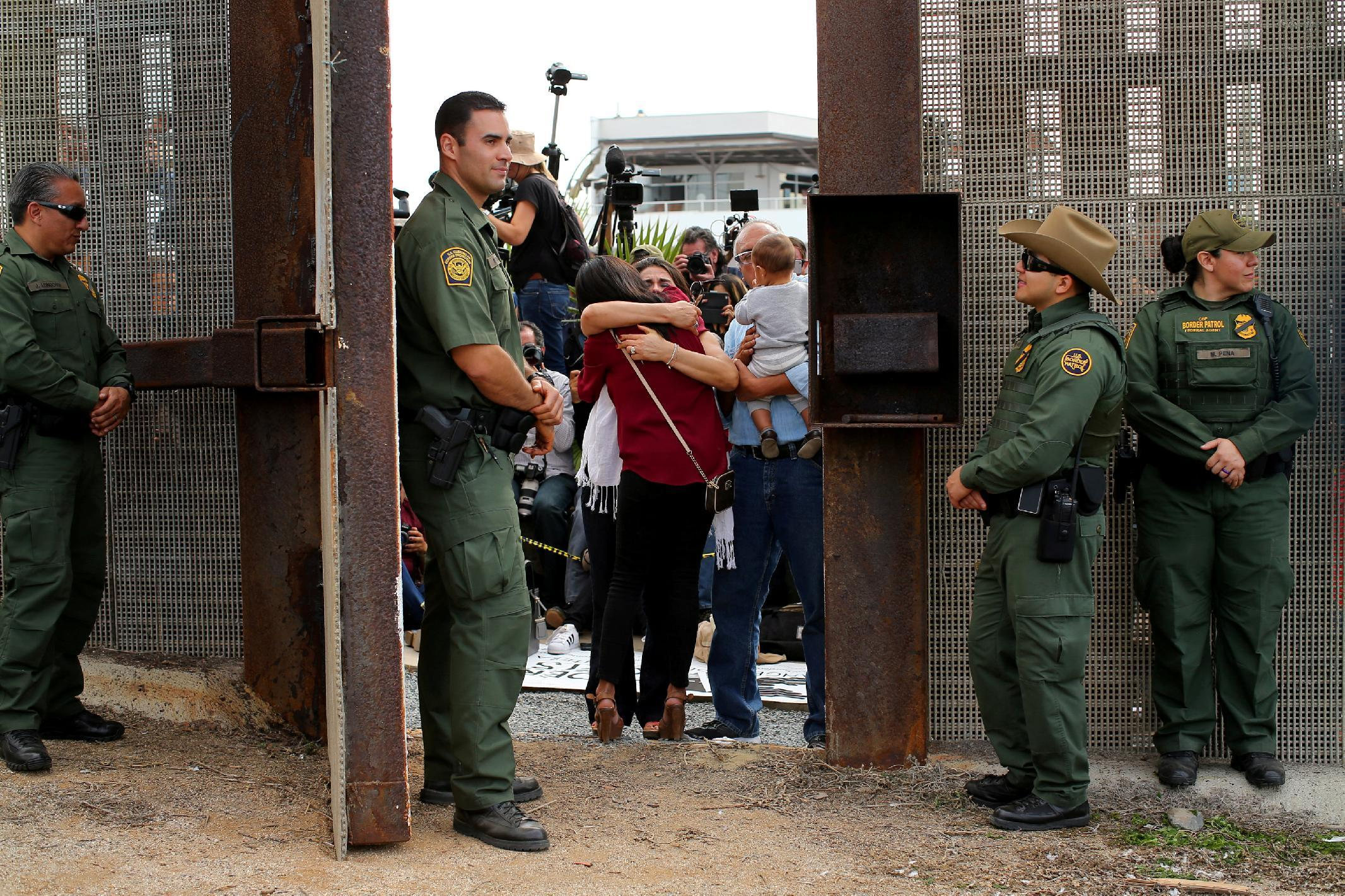 FILE PHOTO - U.S. Border patrol agents stand watch at an open gate on the fence along the Mexico border to allow Delia Valdovinos-Sanchez to embrace Ramona Vargas, as part of Universal Children's Day at the Border Field State Park, California, U.S. on November 19, 2016. REUTERS/Mike Blake/File Photo