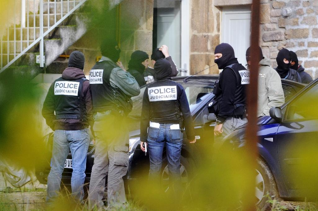 """French criminal investigators stand outside a house in Tarnac, after the arrest of young people suspected of being members of an alleged """"anarchist cell"""" and taking hostage the French high speed train network, November 11, 2008 (AFP Photo/Thierry Zoccolan)"""