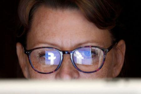 The Facebook logo is reflected on a woman's glasses in this photo illustration taken June 3, 2018. REUTERS/Regis Duvignau/Illustration