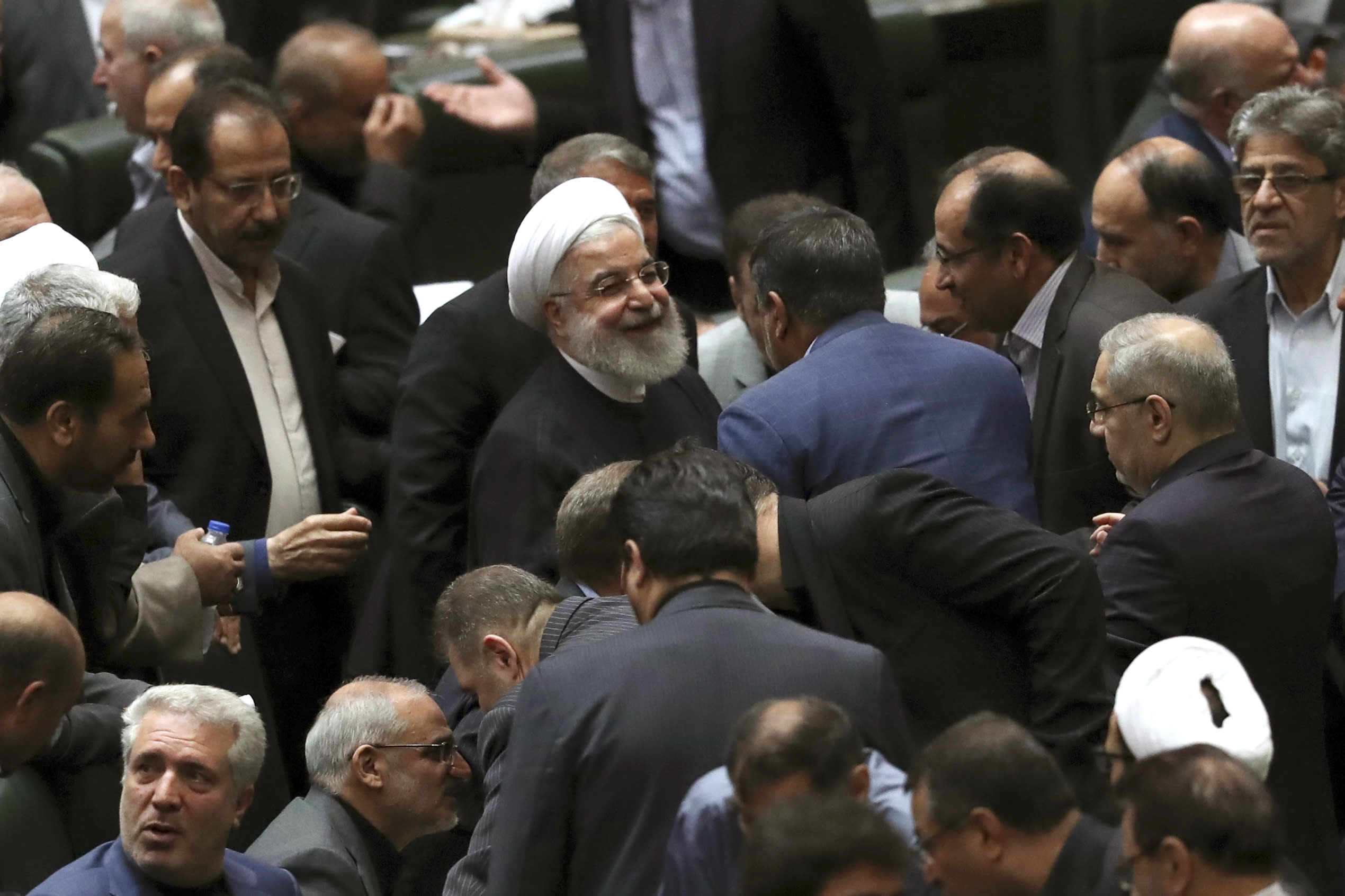 Iranian President Hassan Rouhani, center, listens to a lawmaker after defending his proposed tourism and education ministers, in Tehran, Iran, Tuesday, Sept. 3, 2019. Rouhani said European nations are failing to implement their commitments following the U.S. pullout from the 2015 nuclear deal with Tehran. (AP Photo/Vahid Salemi)