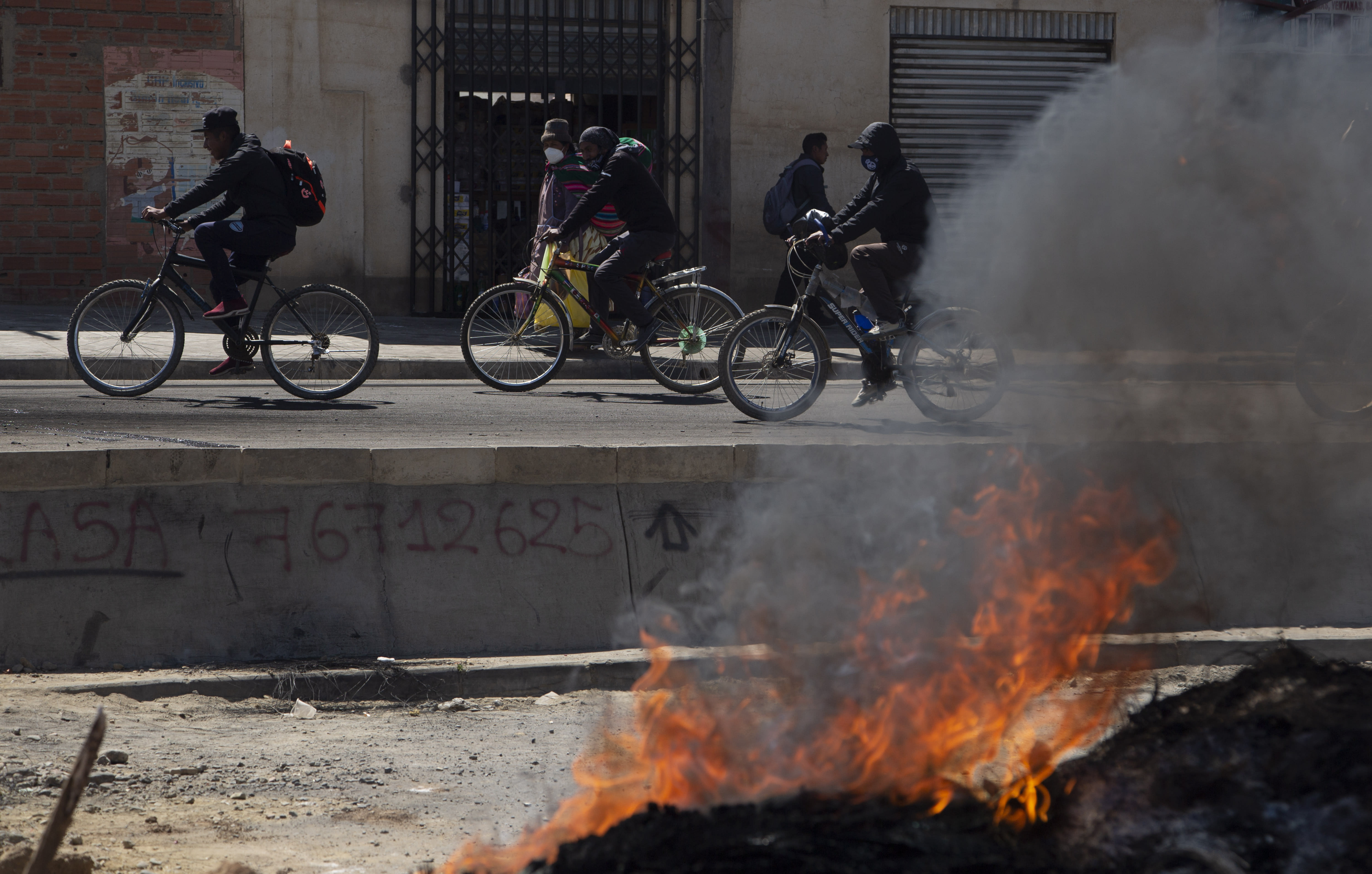 Commuters on bicycles ride past a barricade set up by protesters against the postponement of the presidential election in El Alto, Bolivia, Monday, Aug. 10, 2020. Citing the ongoing new coronavirus pandemic, the nation's highest electoral authority delayed presidential elections from Sept. 6 to Oct. 18, the third time the vote has been delayed. (AP Photo/Juan Karita)