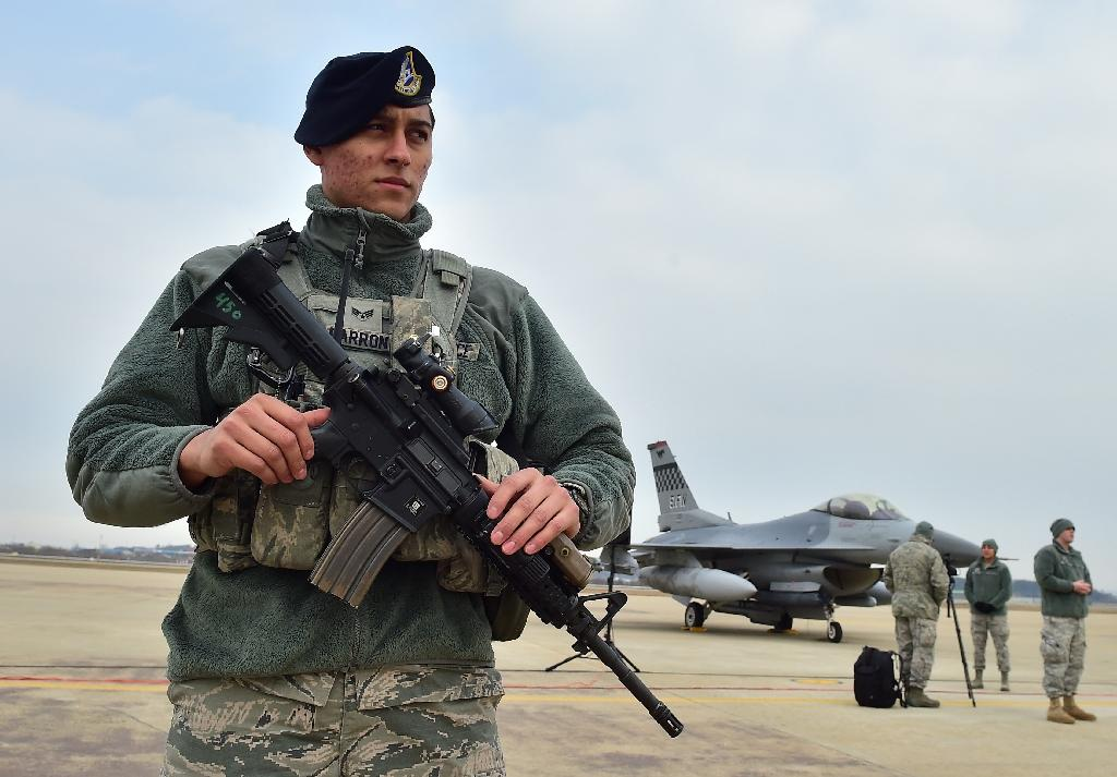 An American soldier (L) stands guard near a US F-16 fighter jet before a press briefing on the flight by a US B-52 Stratofortress over South Korea, at the Osan Air Base in Pyeongtaek, south of Seoul, on January 10, 2016 (AFP Photo/Jung Yeon-Je)