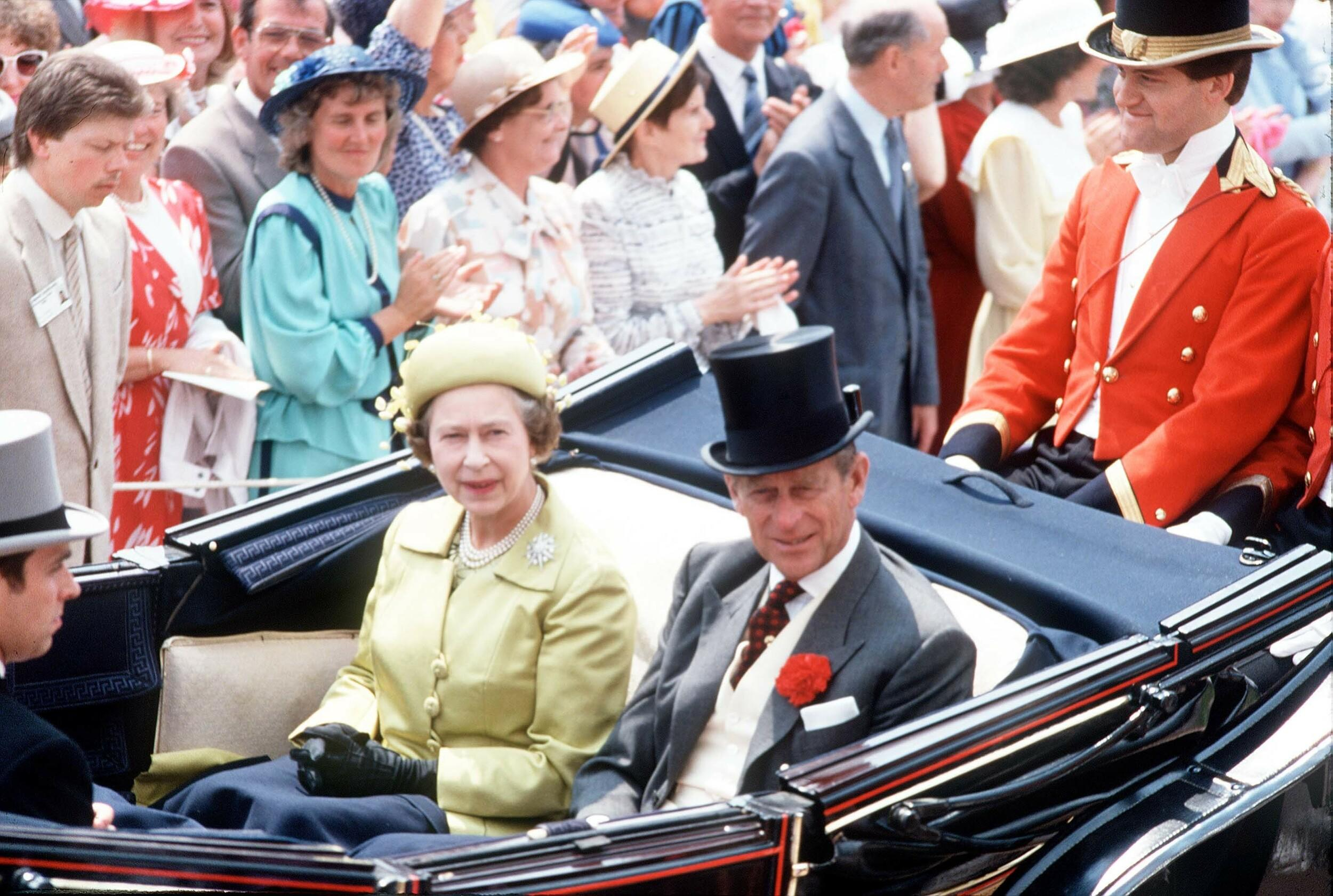 Queen Elizabeth II, the Duke of Edinburgh and the Prince of Wales with butler Paul Burrell, riding at the back of the carriage, at Ascot in June, 1987.